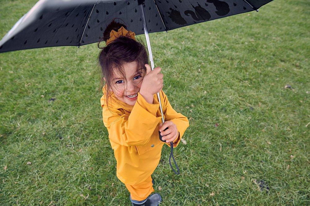 Ein Kind im Park trägt lachend die neue Recycelte Kinder-Regenbekleidung Kollektion von Tchibo