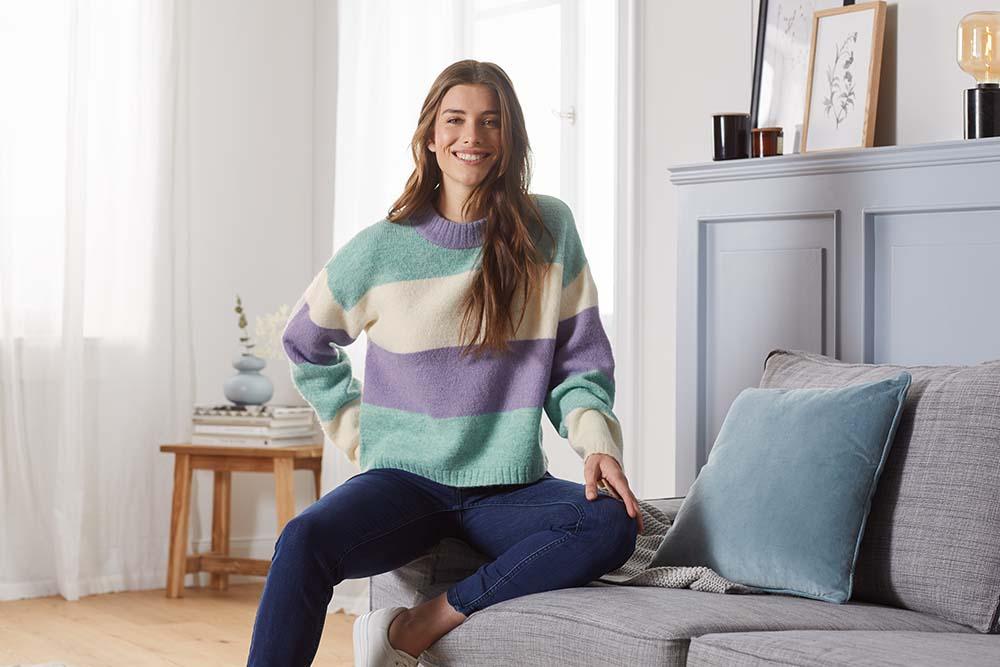Frau sitzt im farbenfrohen Pullover der Herbst-Outfit Kollektion von Tchibo am Sofa.